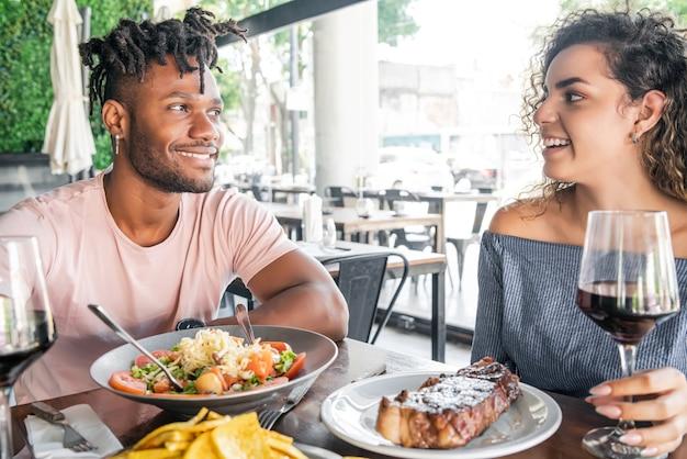 Casal curtindo e passando um bom tempo juntos, tendo um encontro em um restaurante.