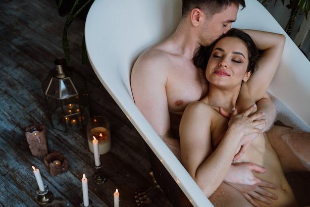 Casal curtindo momentos românticos na banheira da casa