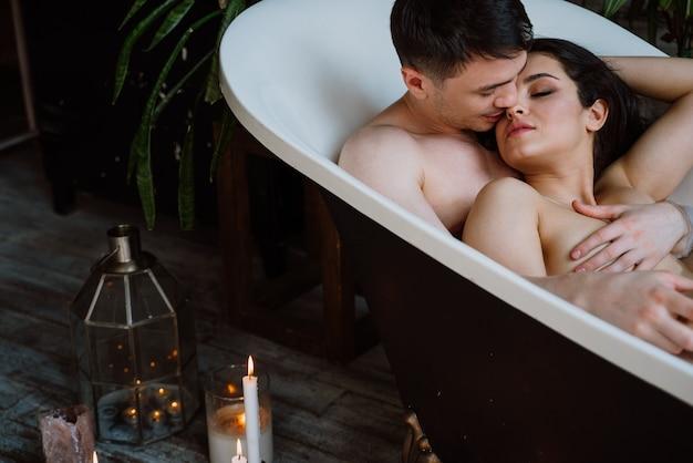 Casal curtindo momentos românticos na banheira da casa Foto Premium