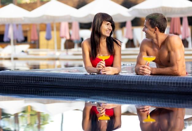Casal curtindo o dia na piscina com drinks