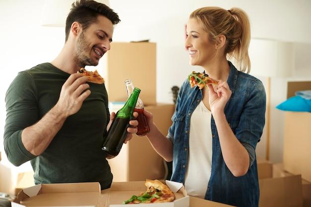 Casal curtindo um drinque e pizza para viagem