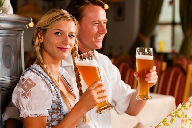Casal da baviera, bebendo cerveja de trigo