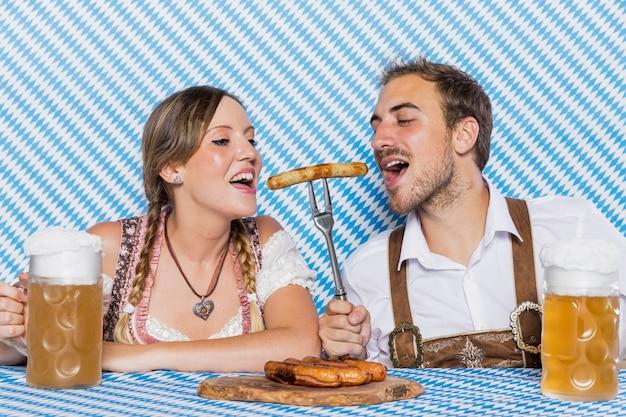 Casal da baviera degustação bratwurst deliciosa