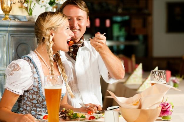 Casal da baviera em comer restaurante