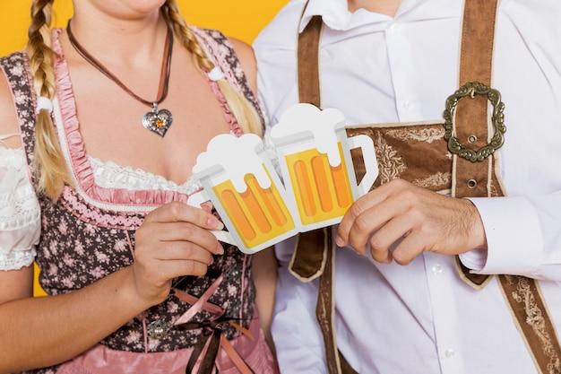 Casal da baviera segurando canecas de cerveja de papel
