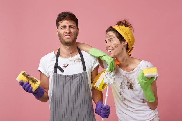 Casal da família arrumando o apartamento: homem descontente de avental segurando uma esponja suja, odiando limpar em pé perto de sua esposa que pede para ele lavar a janela olhando para ele com sorriso e amor