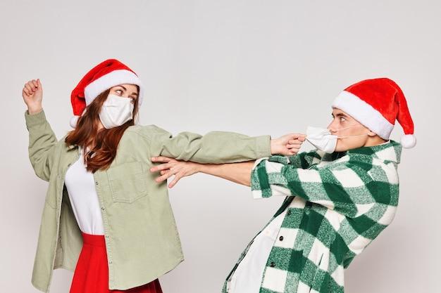 Casal da família com chapéus de natal máscaras médicas emoções feriado ano novo