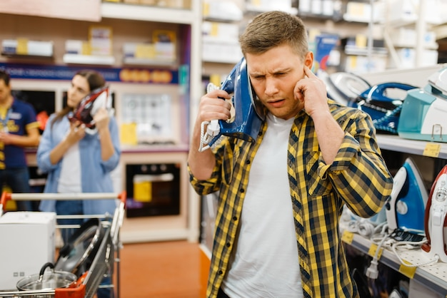 Casal da família detém ferros elétricos como telefones em loja de eletrônicos, piada engraçada. homem e mulher comprando eletrodomésticos no mercado