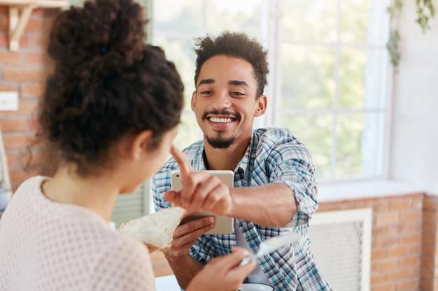 Casal da família diverte-se na cozinha durante o almoço: homem barbudo toca no nariz da namorada que faz sanduíches, sente muito amor e simpatia.