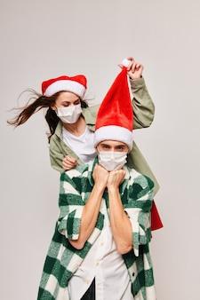Casal da família em chapéus de férias máscara médica de ano novo de natal.