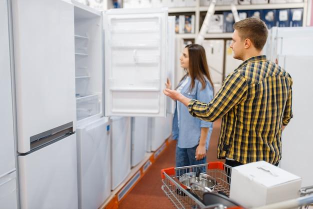 Casal da família escolhendo geladeira na loja de eletrônicos. homem e mulher comprando eletrodomésticos no mercado