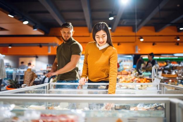 Casal da família na geladeira no supermercado
