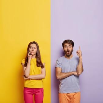Casal da geração do milênio em choque posando contra a parede de duas cores