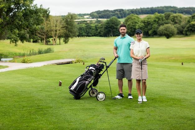 Casal dançando com taco de golfe e bolsa no campo de golfe