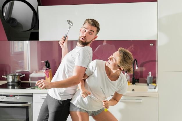 Casal dançando dentro de casa na cozinha vista frontal