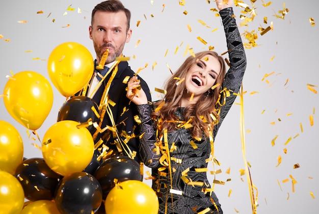 Casal dançando entre confete caindo e serpentina na festa