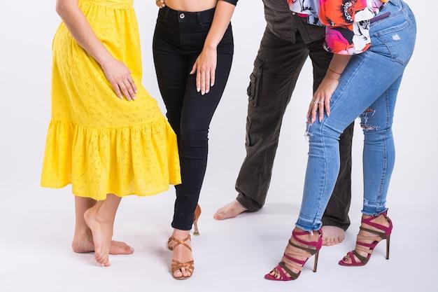 Casal dançando música latina. bachata, merengue, salsa e kizomba. close-up de dançarinos de pernas na sala branca.
