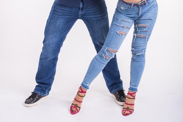 Casal dançando música latina. bachata, merengue, salsa e kizomba. close-up de elegância de pernas posar na sala branca.