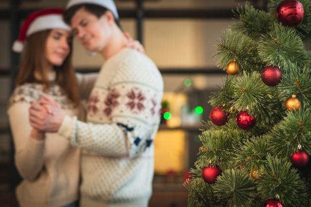 Casal dançando valsa ao lado da árvore de natal