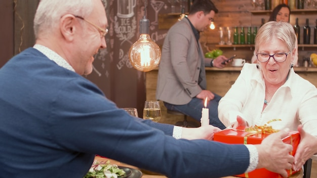 Casal de 60 anos se sentindo bem em um restaurante. homem dando uma caixa de presente para sua esposa. casal feliz. casal sênior alegre.