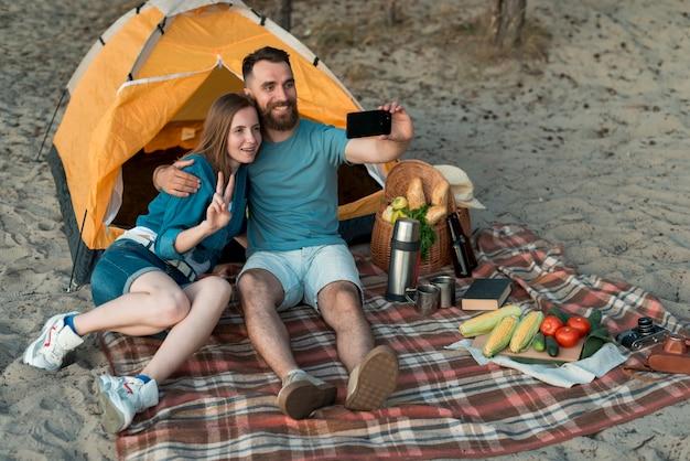 Casal de acampamento tomando uma selfie