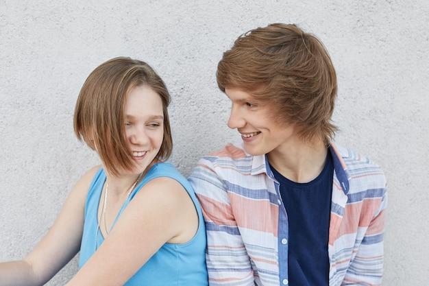 Casal de adolescentes apaixonados, se divertindo, sentados um ao lado do outro, olhando com amor