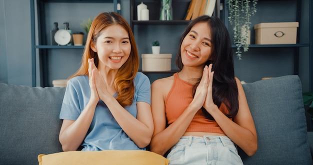 Casal de adolescentes asiáticas se sentindo felizes sorrindo e olhando para a frente enquanto relaxam na sala de estar de casa