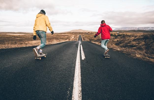 Casal de adolescentes se divertindo patinando e fazendo ladeira abaixo