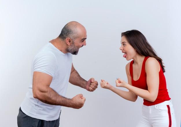 Casal de adultos brigando com raiva, homem e mulher estendendo os punhos e olhando um para o outro isolados