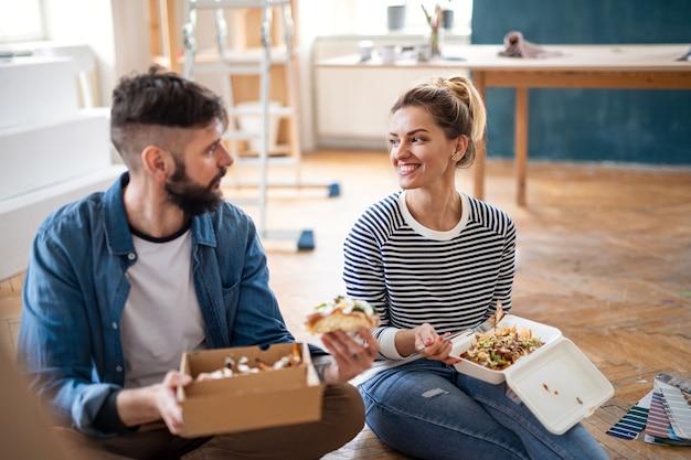 Casal de adultos médios almoçando dentro de casa em casa, relocação, conceito de entrega de comida e diy.