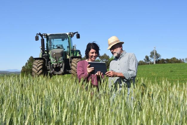 Casal de agricultores em um campo com um tablet digital