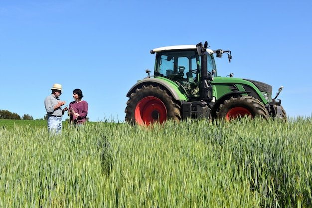 Casal de agricultores em um campo de trigo com um trator