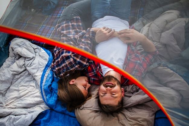 Casal de alto ângulo acampar na barraca
