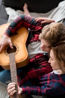 Casal de alto ângulo em casa tocando violão