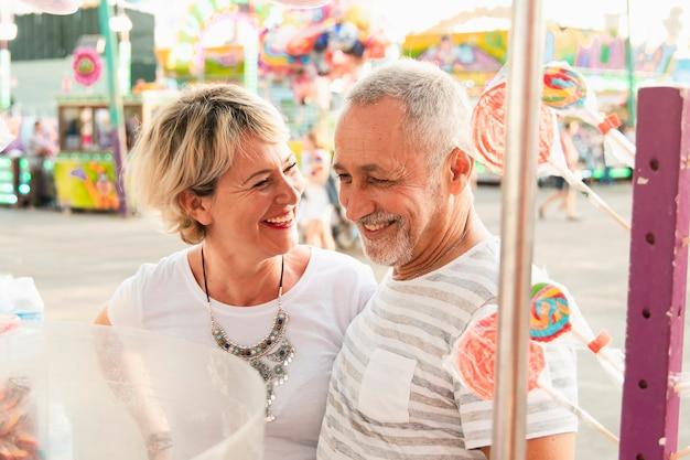 Casal de alto ângulo, sorrindo no parque de diversões