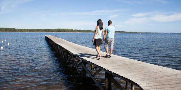 Casal de amantes a pé no pontão do lago durante as férias de primavera