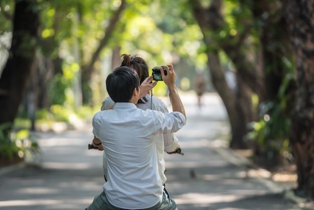 Casal de amantes ciclismo bicicleta por namorada e namorado usar câmera digital tirar uma foto