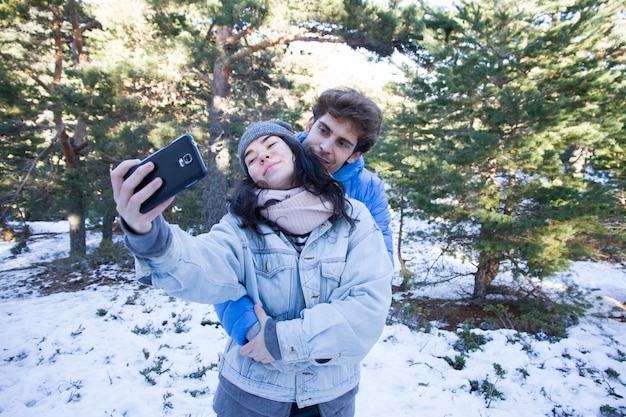 Casal de amantes felizes desfrutando na neve, fazendo um selfie.