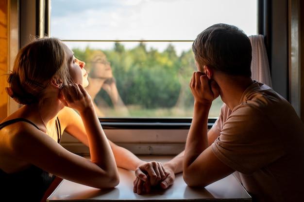 Casal de amantes viajando no trem. retrato de humor de amar pares românticos no vagão, olhando para a janela com auto-reflexões nele. aventura nas férias da família feliz.