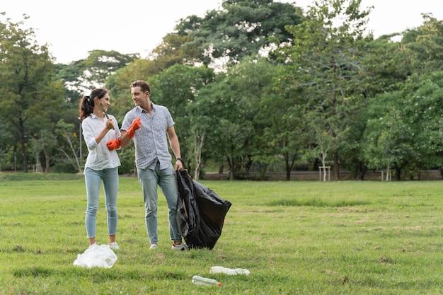 Casal de amantes voluntários usando luvas caminhando para pegar lixo no parque