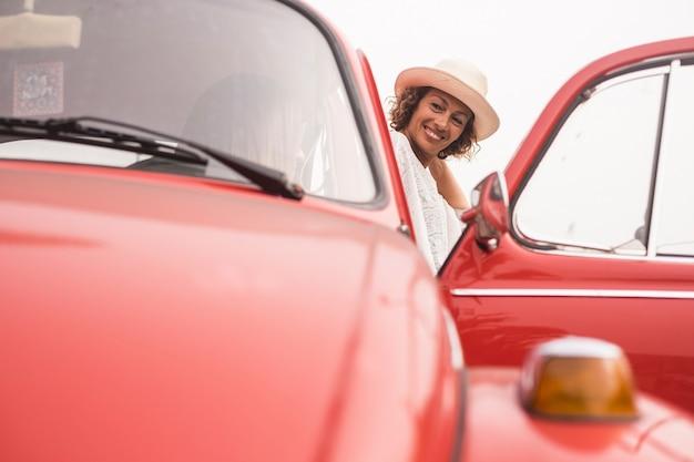Casal de amigas desfrutando da atividade de lazer com um carro retrô vintage vermelho. roupas da moda e pessoas alegres com um estilo de vida bonito e agradável