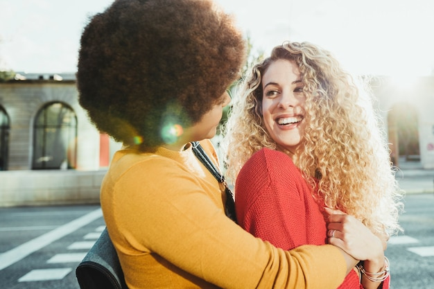 Casal de amigas lésbicas apaixonadas e felizes andando pelas ruas da cidade ao pôr do sol