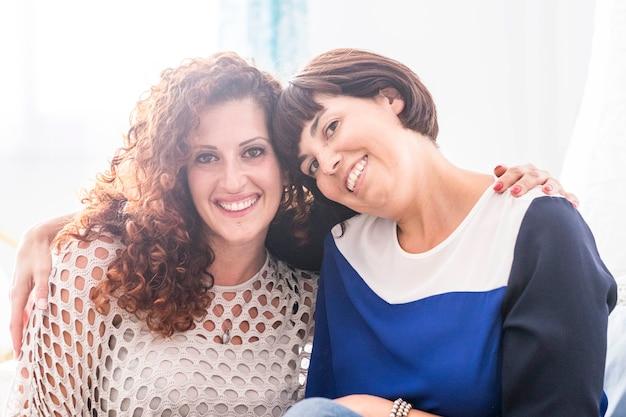 Casal de amigas lindas mulheres jovens se abraçando e sorrindo juntos