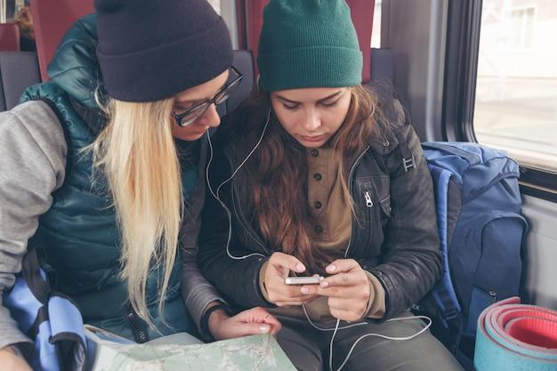 Casal de amigas olhando para o smartphone enquanto no trem