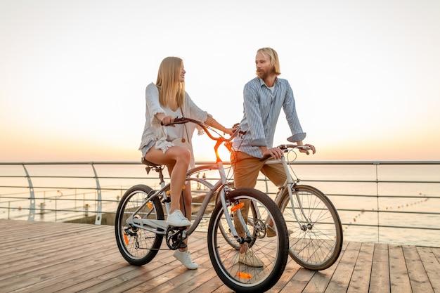 Casal de amigos feliz viajando de bicicleta no verão