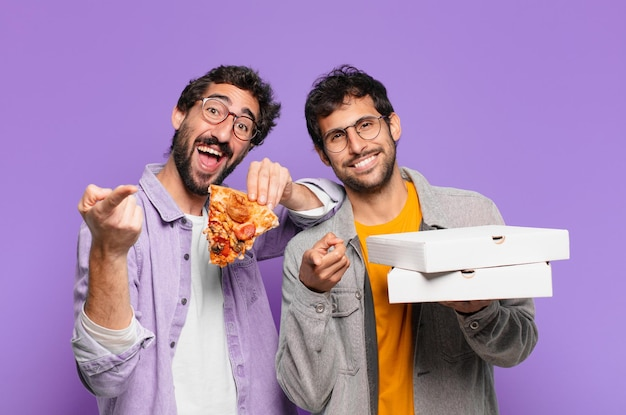 Casal de amigos hispânicos com expressão feliz e segurando pizzas para viagem