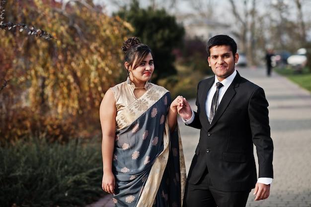 Casal de amigos indianos elegantes e elegantes de mulher em saree e homem de terno caminhando ao ar livre e de mãos dadas.