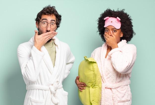 Casal de amigos multirraciais cobrindo a boca com as mãos com uma expressão chocada e surpresa, mantendo um segredo ou dizendo oops. pijama e conceito de casa