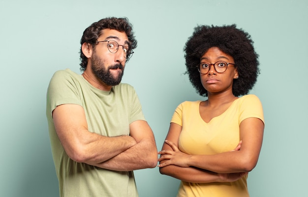Casal de amigos multirraciais encolhendo os ombros, sentindo-se confusos e inseguros, duvidando com os braços cruzados e olhar perplexo