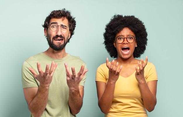 Casal de amigos multirraciais parecendo desesperados e frustrados, estressados, infelizes e irritados, gritando e gritando